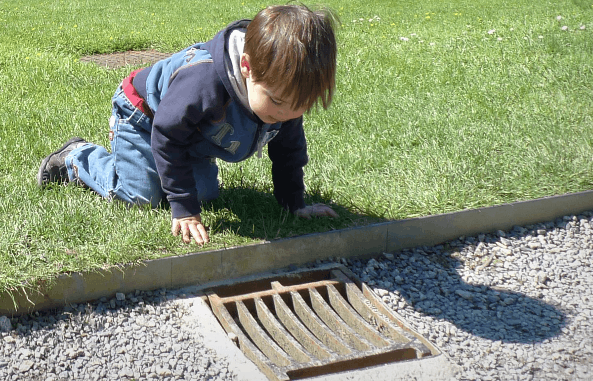child on grass looking down a drain