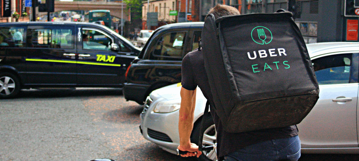 uber eats delivery cyclist crossing a busy street